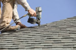 Man working on roof with nail gun. Manassas Roofing Experts 571-371-0018