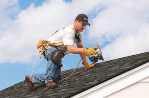 Worker repairing hail damage on shingle home in Manassas, Virginia - Manassas Roofing Experts